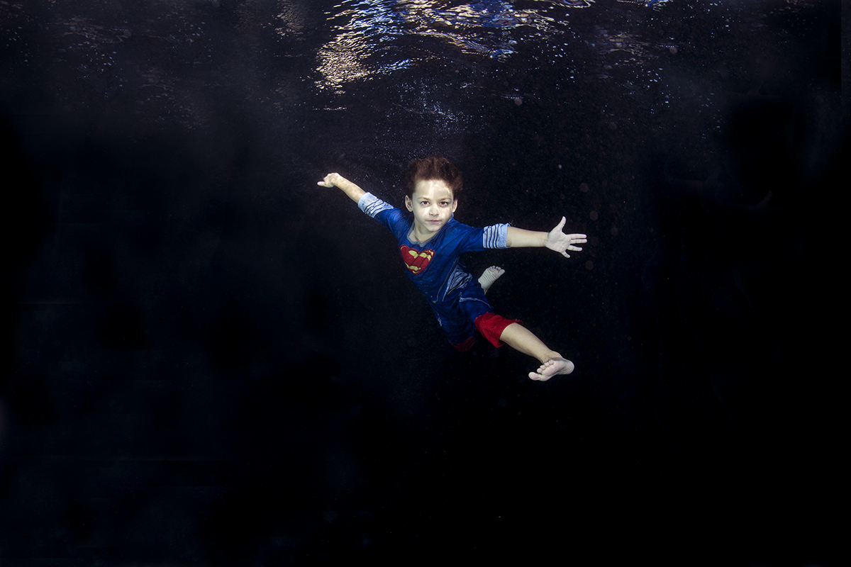 Child in a superman costume underwater