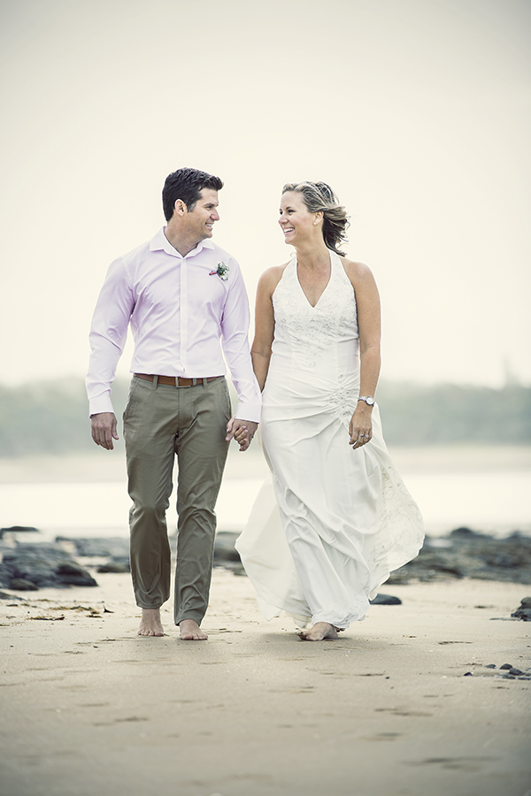 Bride and groom walking on the beach