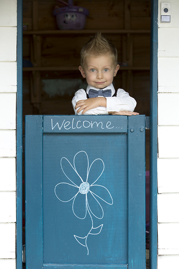A page boy in a bow tie and shirt looking at the camera and leaning on a welcome sign