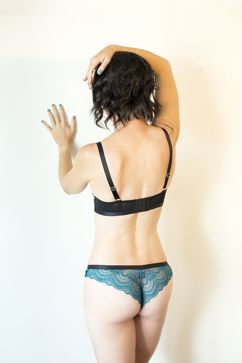 Lady in blue panties facing the wall during a boudoir shoot