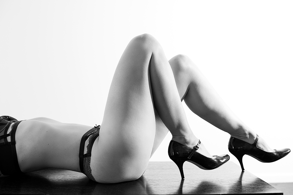 Black and white boudoir Image of a lady lying on the floor showing her legs and high heels