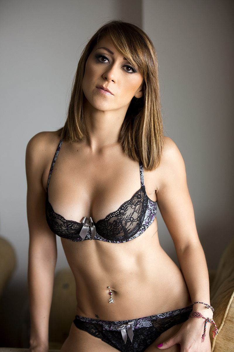 Woman in grey bra and panties looking at the camera during a glamour shoot