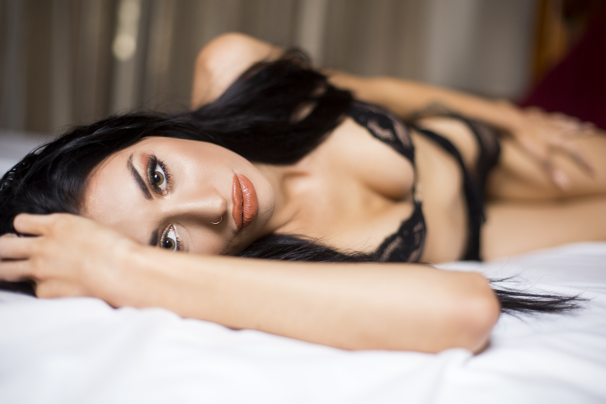 Lady lying on a bed with black lace lingerie looking at the cameraFemale lying on a bed with lingre looking at the camera